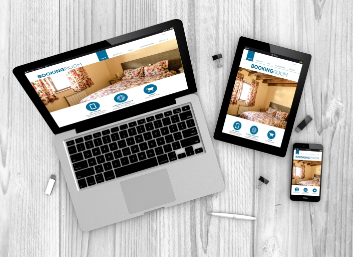 Digital generated devices over a wooden table. laptop, tablet and white smartphone with made up responsive booking website .